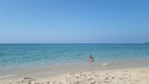 Spiaggia dune - Porto Pino  Mare cristallino con ragazza che fa il bagno