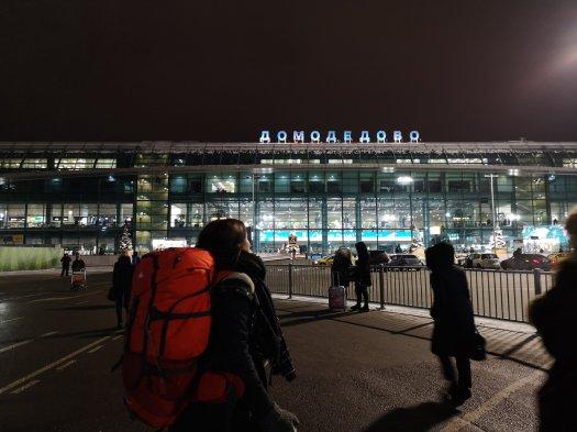 Aeroporto Domodedovo di Mosca e viaggiatrice con zaino in partenza